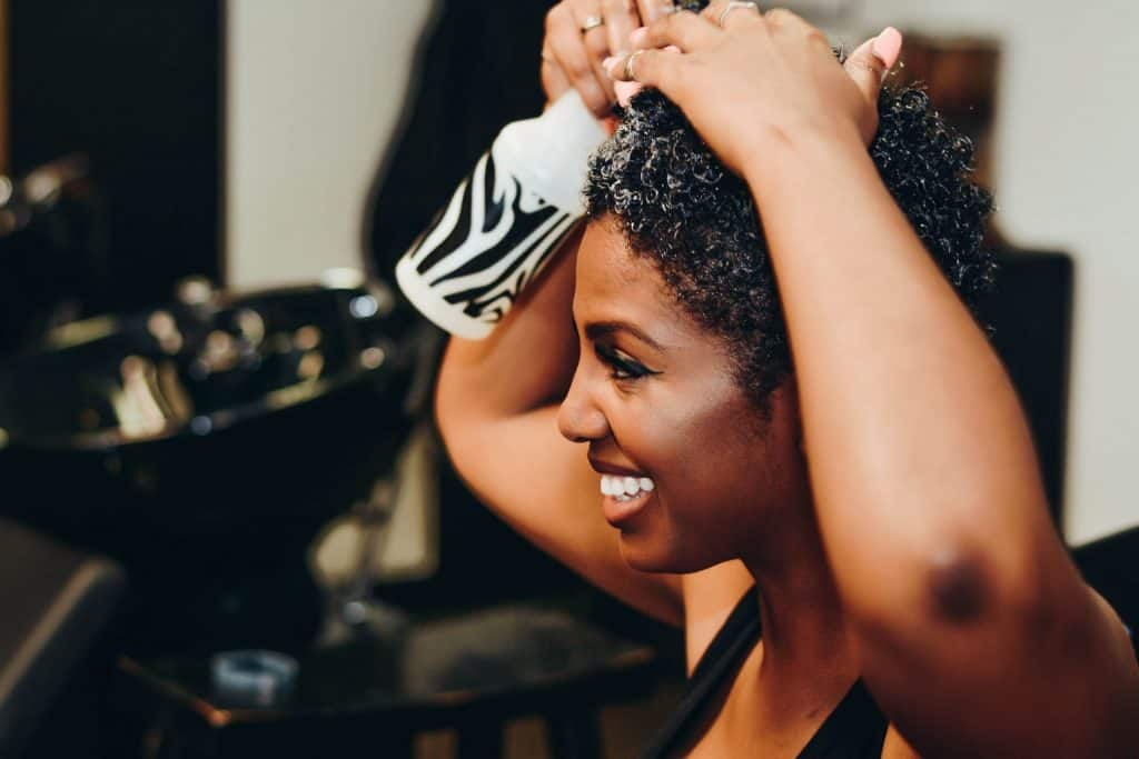 Black woman with short natural hair using a spray bottle to moisturize her hair. She is smiling into a mirror