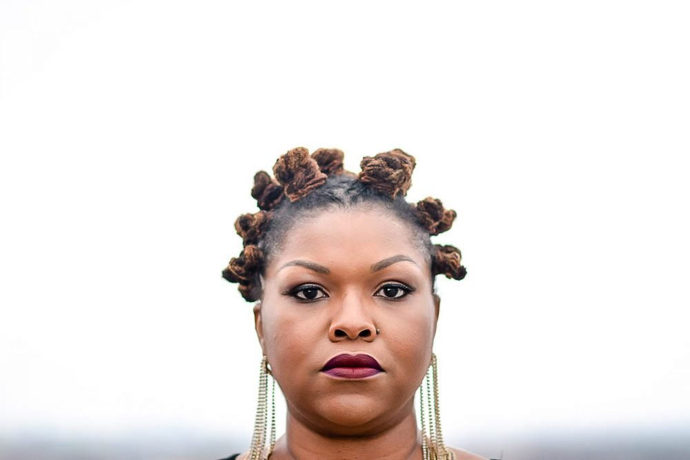 """A Black woman stares into the camera with a straight face, red lipstick, her hair in bantu knots, and long dangling earrings. Her expression conveys the message of the corresponding paragraph: having the """"Moment"""" can make you feel off-balance, irritated, confused, and depressed."""