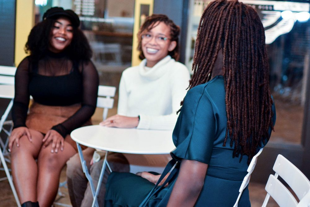 Three Women sit at a table smiling at one another. One wears a blue silk wrap dress, the next wears a black mesh shirt a with a brown suede skirt, and the last woman wear a white sweater, white jeans, and over-the-knee boots.