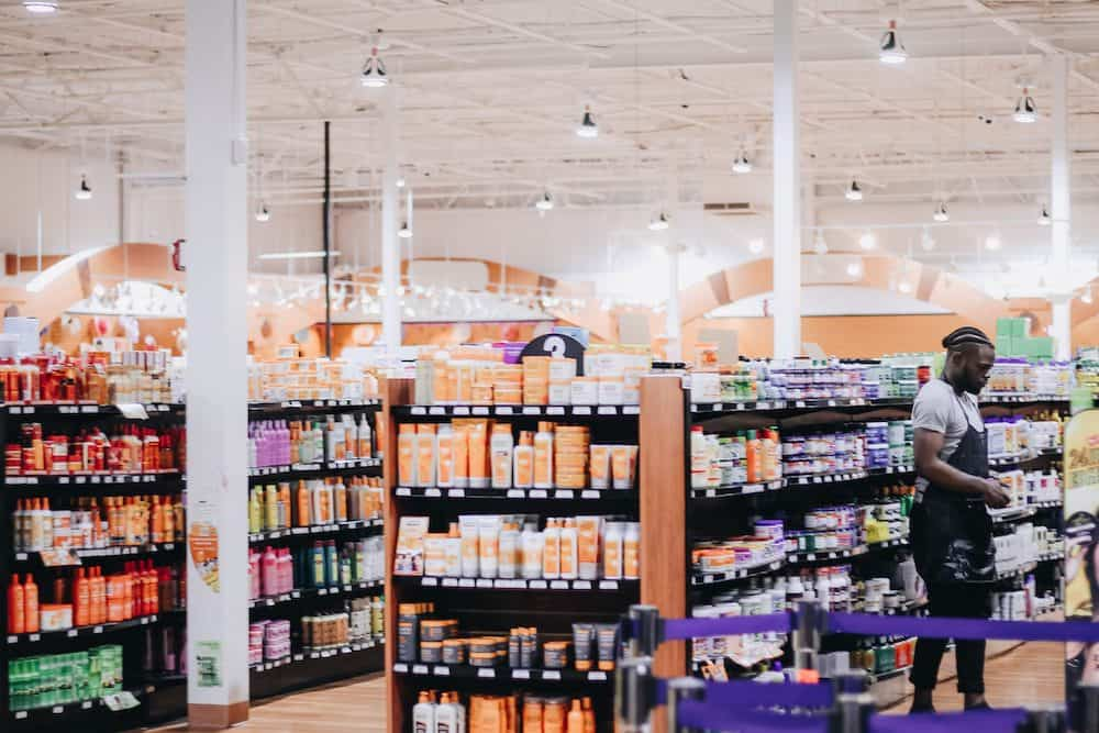 A beauty supply store filled with natural hair products for women with afro-textured hair and looser curls. Black man, an employee, stands over to the right-hand side working.