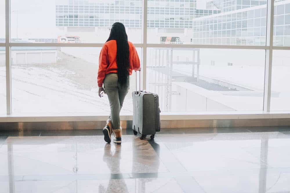 Phase 9: Getting over culture shock: A Black woman stands in an airport looking out the big window at the departing planes. She wears grey jogging pants, orange sweater, and Ugg winter boots. She stand next to her luggage with her phone in her hand. She wears box braids that fall to her hips.