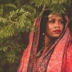 Black woman dressed in Indian/Asian clothing. She wears a red head dressing, a septum piercing (in her nose), and various other golden jewelry in her hair. She stands against a backdrop of lush green trees.