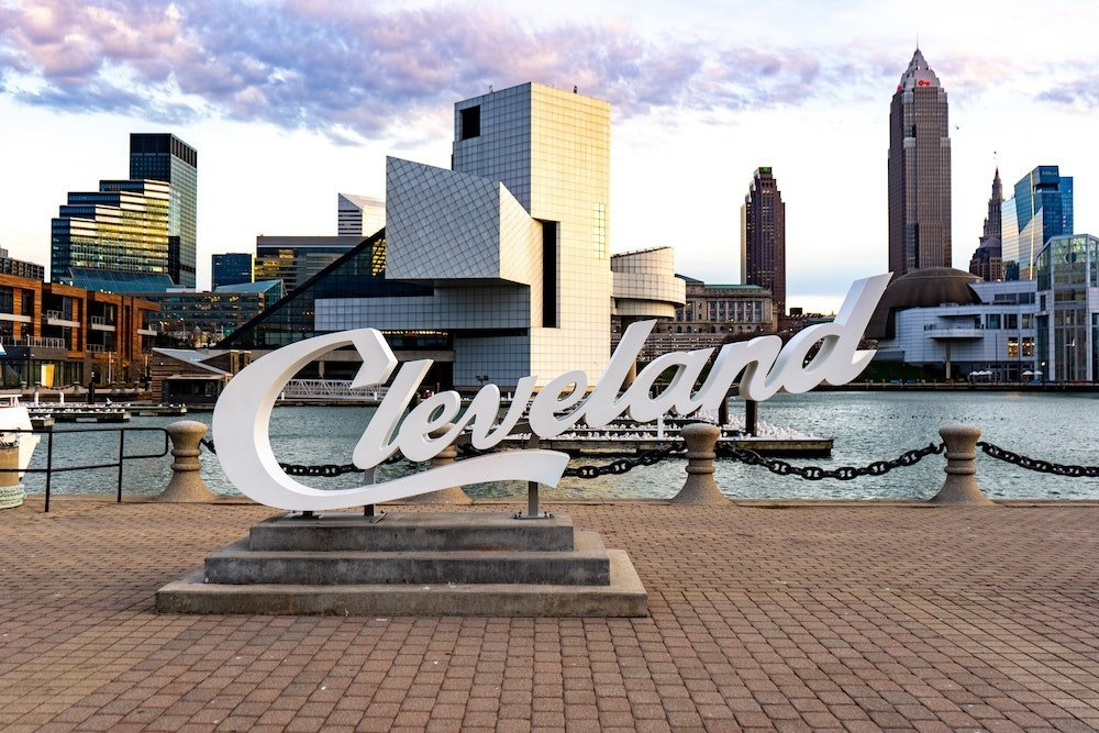 """Returning home and feeling relieved that your experience with culture is over. Or so you thought...A photo of the white """"Cleveland"""" sign near the docks in Downtown Cleveland, Ohio. Behind the sign, a snippet of the city skyline is visible."""