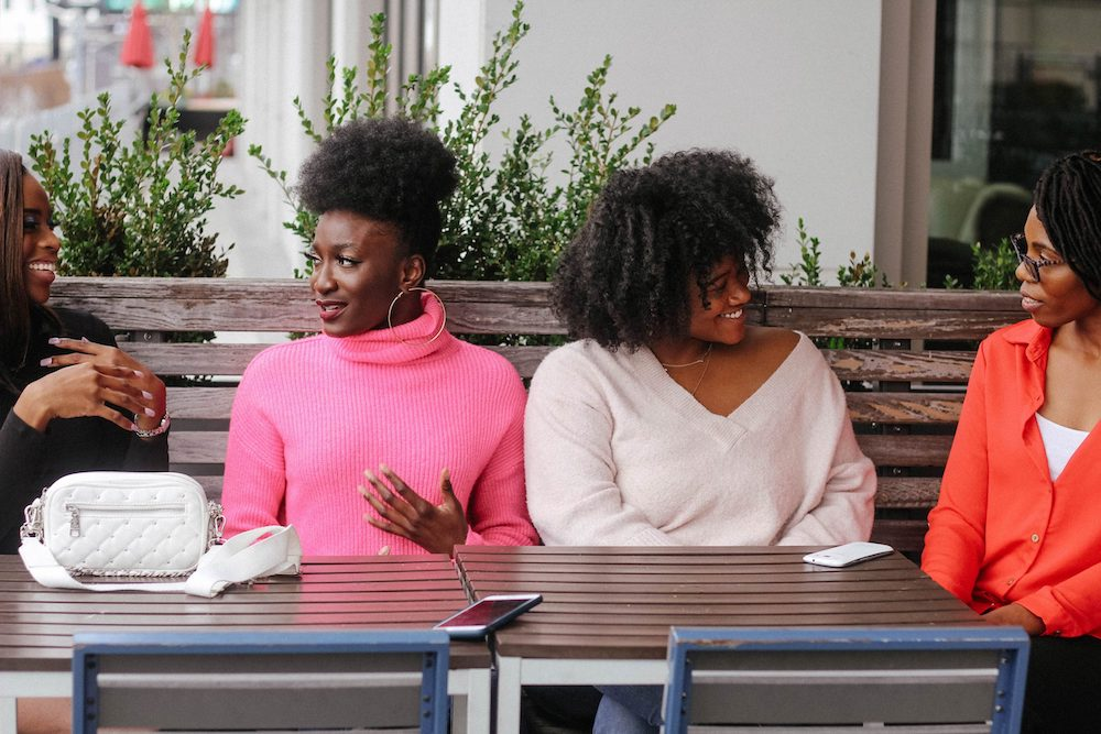 A group of four women sit at a table, discussing something. They each wear sweaters, one bright bubblegum pink, the next wearing black, the next wear cream, and the last one wearing a bright orange cardigan. They look happy and interested in the discussion.